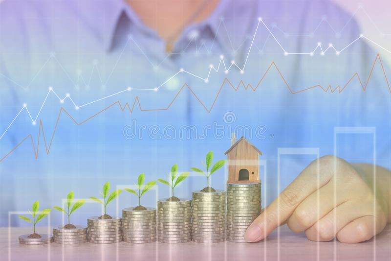 Χρηματοδότηση, χέρι γυναικών που κρατά το πρότυπο σπίτι με την ανάπτυξη εγκαταστάσεων στο σωρό των χρημάτων νομισμάτων και τη γρα απεικόνιση αποθεμάτων