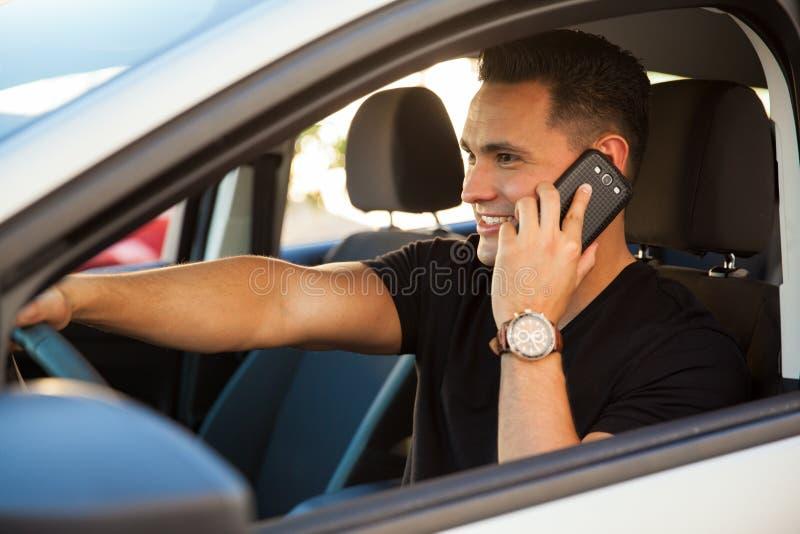 Χρησιμοποίηση ενός τηλεφώνου και οδήγηση στοκ εικόνα