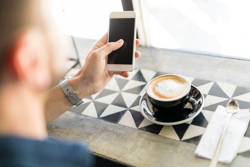 Χρησιμοποίηση ενός τηλεφώνου πίνοντας κάποιο καφέ στοκ εικόνες