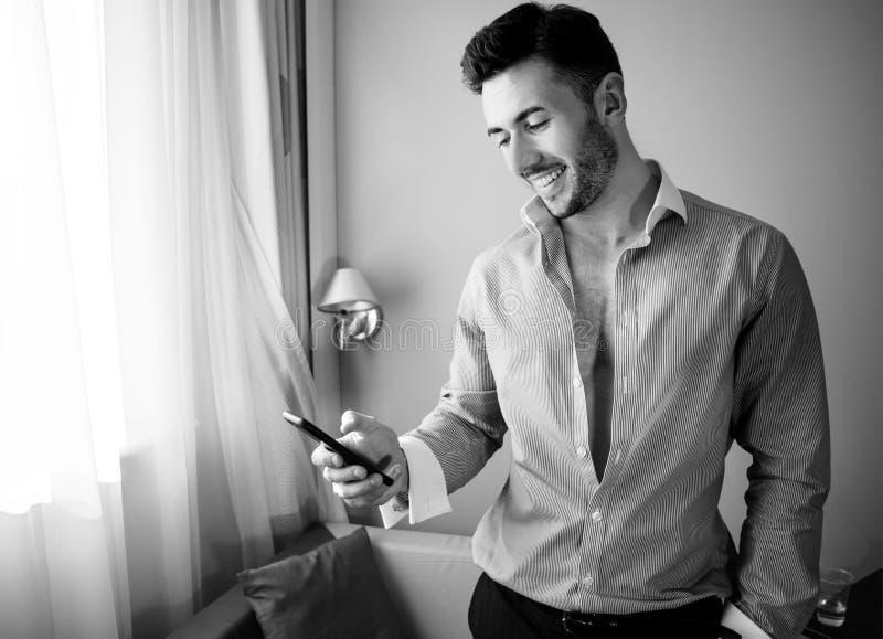 Χρησιμοποίηση επιχειρησιακών excecutive, επαγγελματική ατόμων κινητή, τηλεφωνική συσκευή κυττάρων στεμένος μπροστά από το παράθυρ στοκ εικόνες