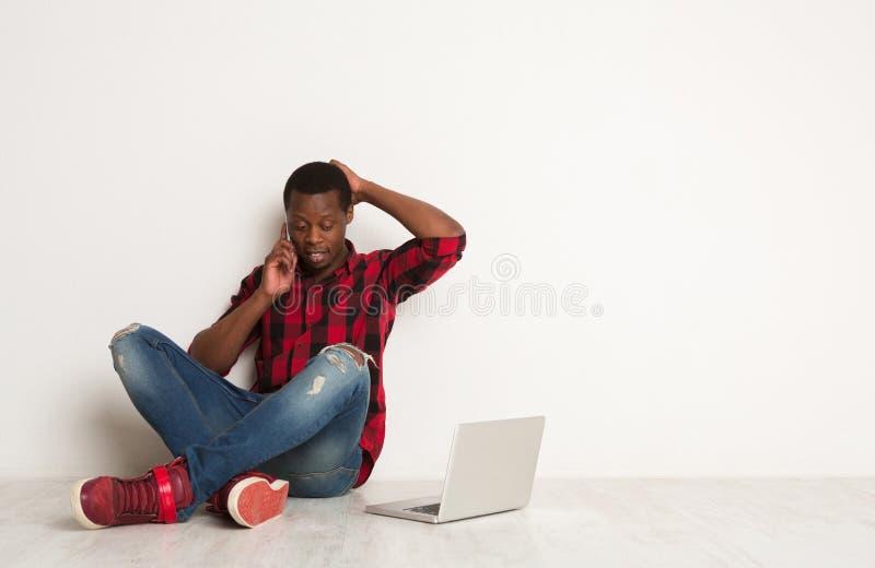 Χρησιμοποίηση μαύρων σκέψης κινητή και συνεδρίαση lap-top στο πάτωμα στούντιο στοκ εικόνες