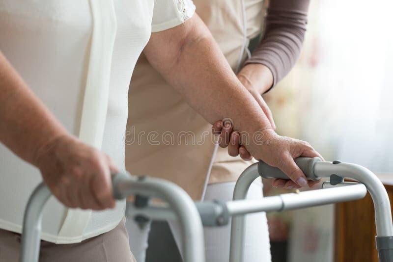 Χρησιμοποίηση του περιπατητή κατά τη διάρκεια της φυσιοθεραπείας στοκ φωτογραφία