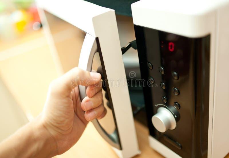 Χρησιμοποίηση του φούρνου μικροκυμάτων στοκ φωτογραφία με δικαίωμα ελεύθερης χρήσης