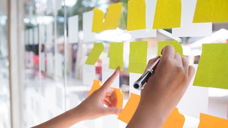 Χρησιμοποίηση χεριών μετα αυτό κολλώδης σημείωση με το 'brainstorming' σε χαρτί σημειώσεων στοκ εικόνα