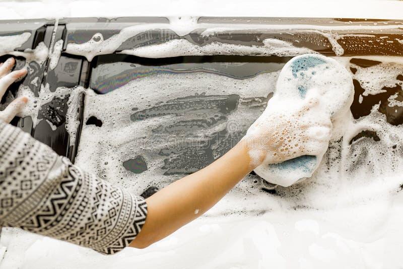 Χρησιμοποιήστε δεξή σας για να πιάσετε το σφουγγάρι και να γυαλίσετε το παράθυρο αυτοκινήτων στοκ εικόνες