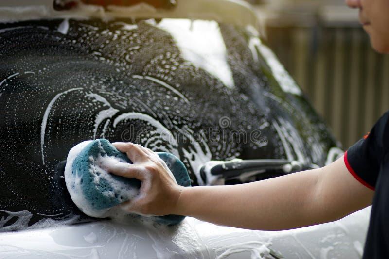 Χρησιμοποιήστε δεξή σας για να πιάσετε το σφουγγάρι και να γυαλίσετε το παράθυρο αυτοκινήτων Πλύσιμο αυτοκινήτων έννοιας στοκ φωτογραφία με δικαίωμα ελεύθερης χρήσης
