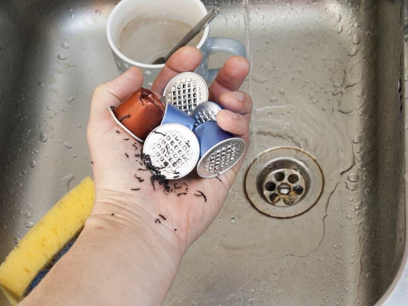 Χρησιμοποιημένες κάψες καφέ χεριών εκμετάλλευση στοκ εικόνα