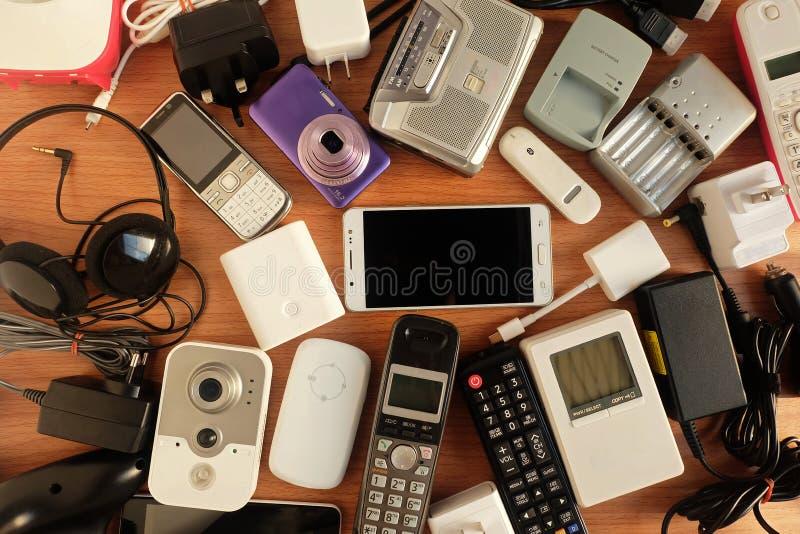 Χρησιμοποιημένες σύγχρονες ηλεκτρονικές συσκευές για την καθημερινή χρήση στο ξύλινο πάτωμα, την επαναχρησιμοποίηση και την ανακύ στοκ φωτογραφία