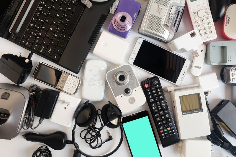 Χρησιμοποιημένες σύγχρονες ηλεκτρονικές συσκευές για την καθημερινή χρήση στο άσπρο πάτωμα, την επαναχρησιμοποίηση και την ανακύκ στοκ εικόνες