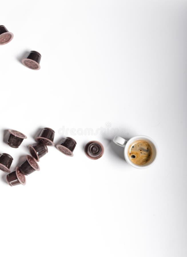 Χρησιμοποιημένοι coffe κάψες και καφές espresso πέρα από ένα άσπρο υπόβαθρο στοκ εικόνες