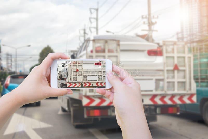 Χρησιμοποιώντας το smartphone φωτογραφίστε το σπασμένο αυτοκίνητο στο φορτηγό ρυμούλκησης μετά από το τροχαίο ατύχημα στοκ εικόνες με δικαίωμα ελεύθερης χρήσης