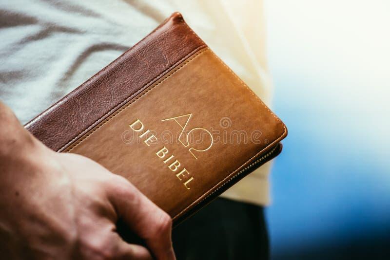 Χριστιανικός ιεροκήρυκας: Ο νεαρός άνδρας κρατά τη Βίβλο, επίκληση στοκ φωτογραφία