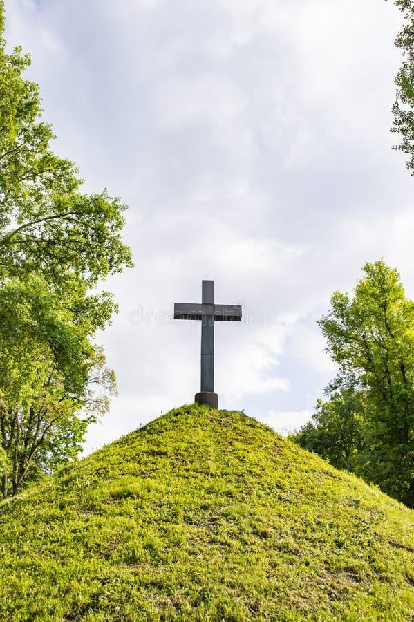 Χριστιανικός σταυρός σε έναν πράσινο λόφο λόφων κάτω από έναν νεφελώδη ουρανό στοκ εικόνες