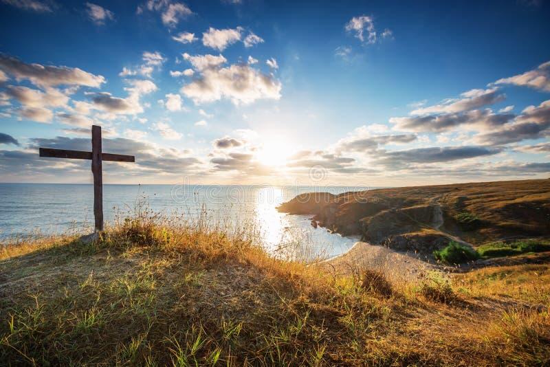 Χριστιανικός σταυρός σε μια άγρια παραλία και μια θαυμάσια ανατολή στοκ φωτογραφίες