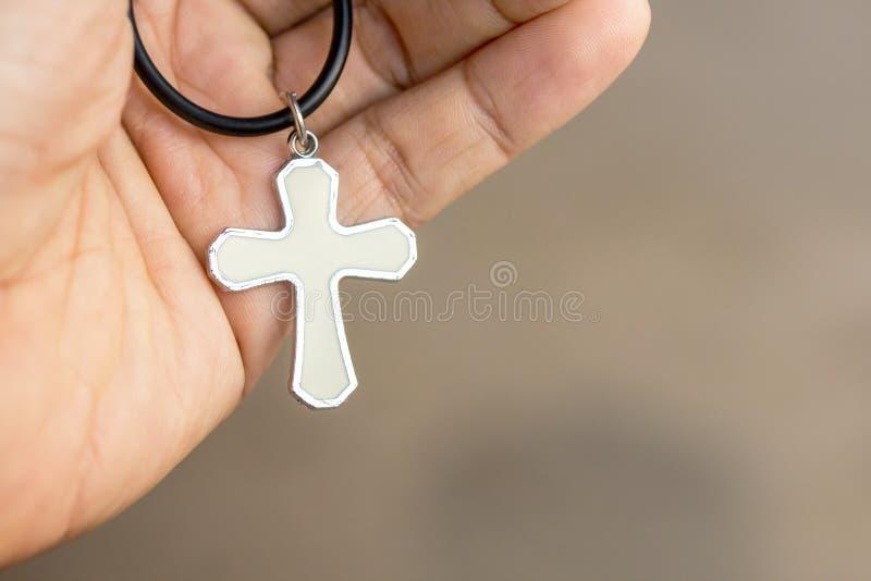 Χριστιανικός σταυρός υπό εξέταση με το θολωμένο bokeh ελαφρύ υπόβαθρο στοκ εικόνες