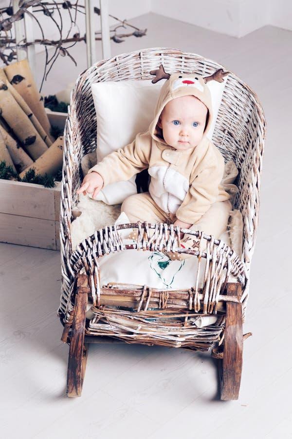 Χριστουγέννων δασικός knurled ευρύς χειμώνας ιχνών πρωινού χιονώδης Μικρό κορίτσι στη συνεδρίαση ελαφιών jumpsuit σε ένα έλκηθρο στοκ φωτογραφίες