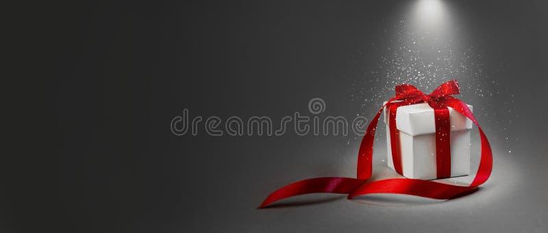 Χριστουγέννων δώρων άσπρο κιβωτίων κόκκινο κορδελλών σκοτεινό γκρίζο υποβάθρου έννοιας φωτισμένο νύχτα έμβλημα σύνθεσης διακοπών  στοκ εικόνα με δικαίωμα ελεύθερης χρήσης