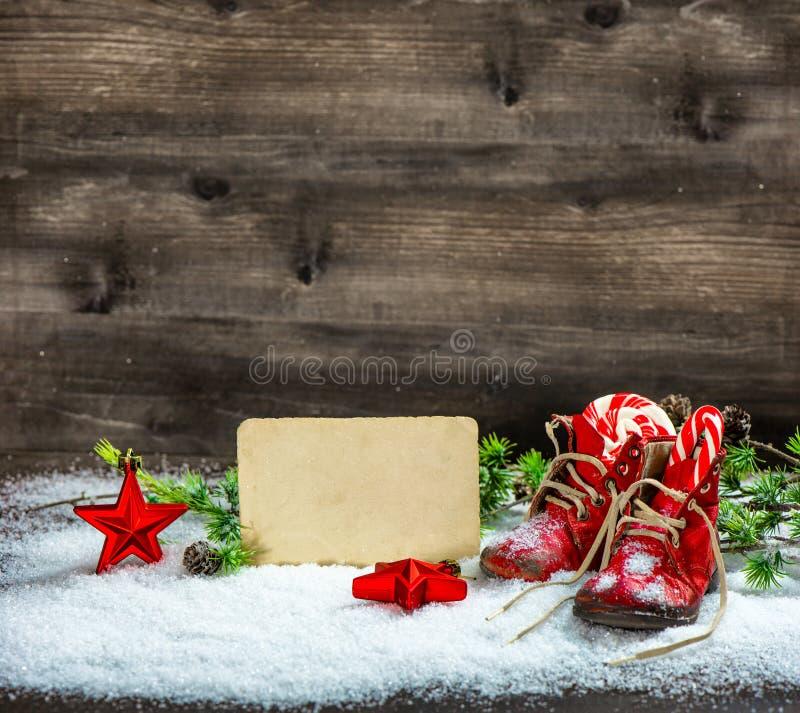 Χριστουγέννων διακοσμήσεων κόκκινη κάρτα χιονιού παπουτσιών μωρών αστεριών παλαιά στοκ φωτογραφία με δικαίωμα ελεύθερης χρήσης