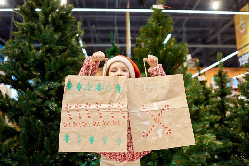 Χριστουγεννιάτικα δώρα αγοράς μικρών κοριτσιών στοκ φωτογραφία με δικαίωμα ελεύθερης χρήσης