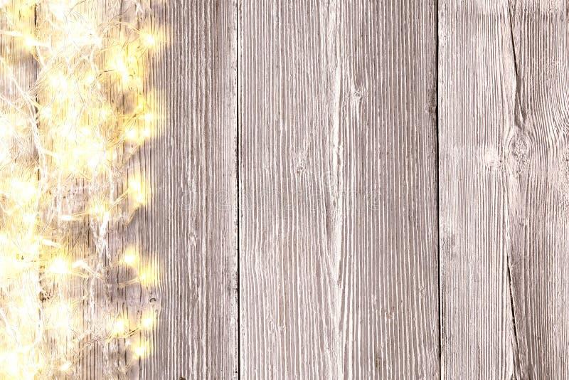 Χριστουγεννιάτικα φώτα σε ξύλινο φόντο, διακοσμήσεις Xmas σε ξύλινες σανίδες στοκ εικόνα