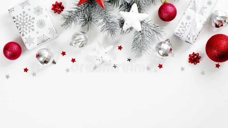 Χριστουγεννιάτικες διακοπές με λευκά υποκαταστήματα πεύκου, κόκκινα και ασημένια παράσημα Περίγραμμα επάνω πλαισίου Xmas από στοκ εικόνες