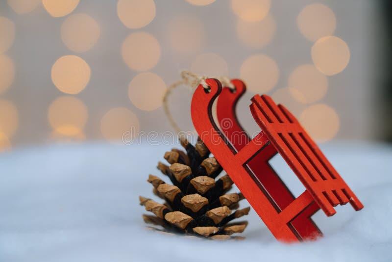 Χριστουγεννιάτικη σύνθεση με κόκκινο ξύλινο έλκηθρο του Άγιου Βασίλη, κωνικό έλκηθρο και μπάλες δέντρου Xmas πάνω από θαμπό φως στοκ εικόνες με δικαίωμα ελεύθερης χρήσης