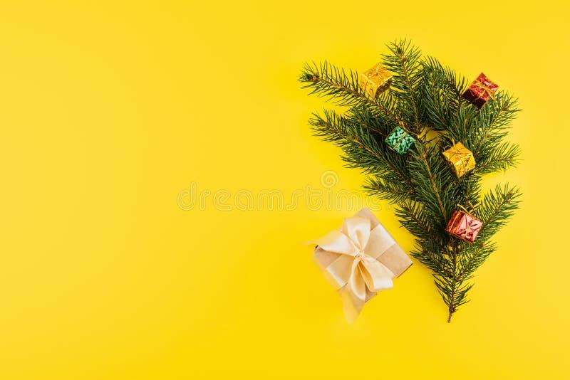 Χριστουγεννιάτικη σύνθεση με τα κλαδιά του Conifer Evergreen και το κουτί δώρων σε κίτρινο φόντο Ελάχιστα Χριστούγεννα και 2020 στοκ φωτογραφία με δικαίωμα ελεύθερης χρήσης