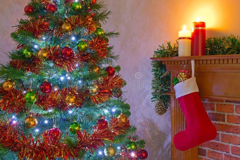 Χριστουγεννιάτικο δέντρο και γυναικεία κάλτσα πέρα από την εστία στοκ φωτογραφία