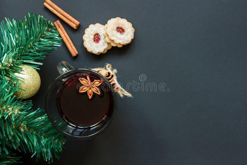 Χριστουγεννιάτικο δέντρο και wineglass του θερμαμένου κρασιού με τα μπισκότα και του πορτοκαλιού στη μαύρη άποψη επιτραπέζιων κορ στοκ εικόνες