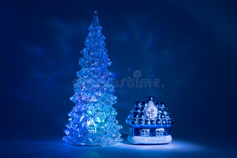 Χριστουγεννιάτικο δέντρο παιχνιδιών που λάμπει με τα όμορφα βόρεια φω'τα σκιών κοντά στο σπίτι από ένα παραμύθι σε ένα σκούρο μπλ στοκ εικόνες με δικαίωμα ελεύθερης χρήσης