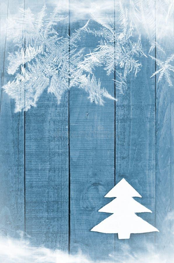 Χριστουγεννιάτικο δέντρο που γίνεται από το λευκό που γίνεται αισθητό στο ξύλινο, μπλε υπόβαθρο Εικόνα χιονιού flaks Διακόσμηση χ στοκ εικόνες