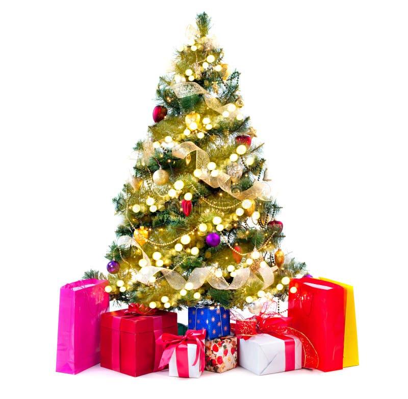 Χριστουγεννιάτικο δέντρο που διακοσμείται με τα μπιχλιμπίδια, τις γιρλάντες και τα δώρα στοκ εικόνες