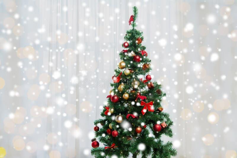 Χριστουγεννιάτικο δέντρο στο καθιστικό πέρα από την κουρτίνα παραθύρων στοκ εικόνα