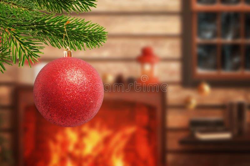 Χριστουγεννιάτικο δέντρο με τη διακοσμητική κόκκινη σφαίρα στο πρώτο πλάνο στοκ εικόνες