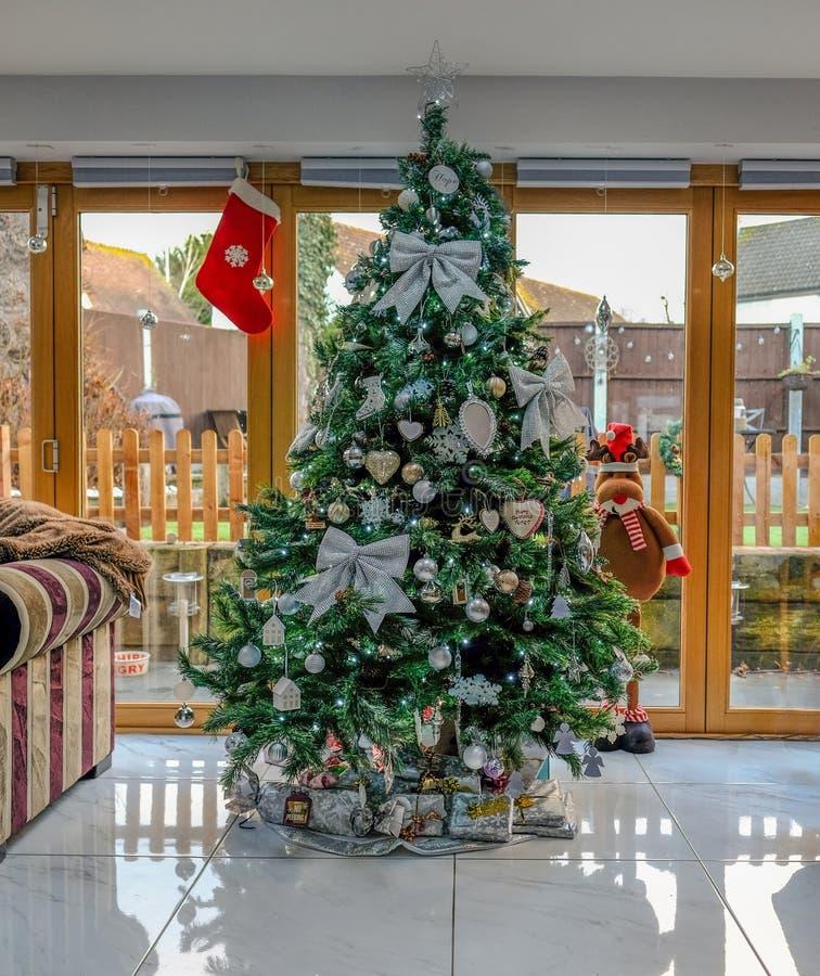 Χριστουγεννιάτικο δέντρο που διακοσμείται με τα ασημένια τόξα και τα μπιχλιμπίδια στοκ φωτογραφίες