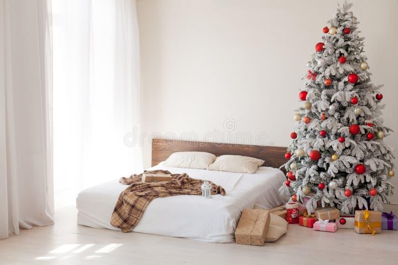 Χριστουγεννιάτικο δέντρο σε μια άσπρη κρεβατοκάμαρα με το εσωτερικό κρεβατιών των νέων δώρων έτους στοκ φωτογραφία με δικαίωμα ελεύθερης χρήσης