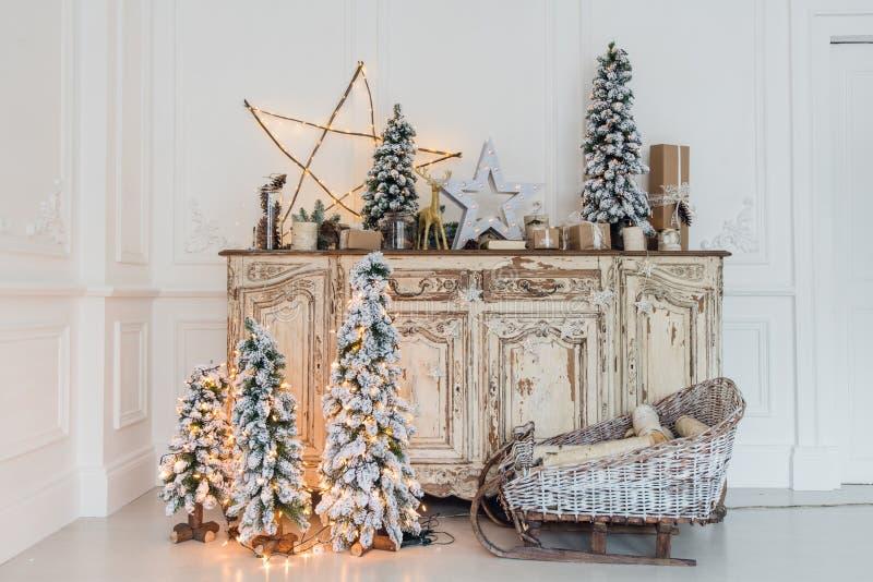 Χριστουγεννιάτικο δέντρο στο ξύλινο γραφείο θωρακικών των συρταριών κομό εσωτερικό, που διακοσμείται στο άσπρο με τα τεχνητά λουλ στοκ φωτογραφίες
