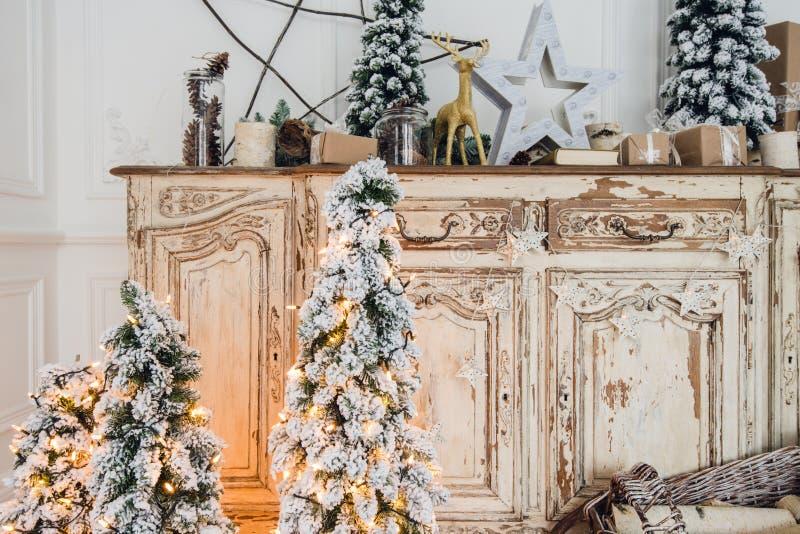 Χριστουγεννιάτικο δέντρο στο ξύλινο γραφείο θωρακικών των συρταριών κομό εσωτερικό, που διακοσμείται στο άσπρο με τα τεχνητά λουλ στοκ φωτογραφία