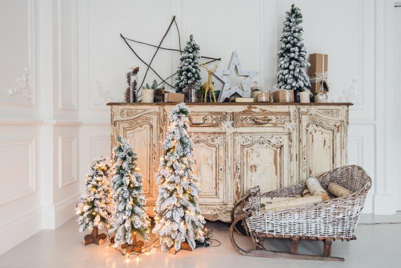 Χριστουγεννιάτικο δέντρο στο ξύλινο γραφείο θωρακικών των συρταριών κομό εσωτερικό, που διακοσμείται στο άσπρο με τα τεχνητά λουλ στοκ φωτογραφία με δικαίωμα ελεύθερης χρήσης
