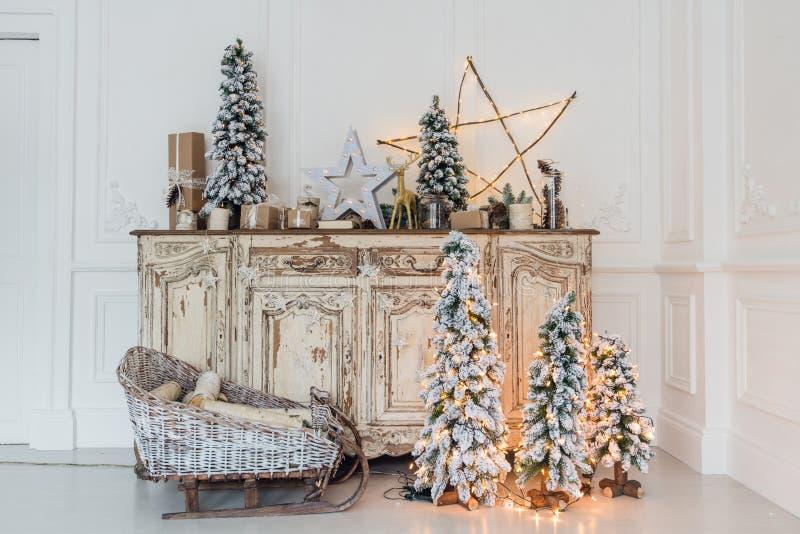 Χριστουγεννιάτικο δέντρο στο ξύλινο γραφείο θωρακικών των συρταριών κομό εσωτερικό, που διακοσμείται στο άσπρο με τα τεχνητά λουλ στοκ εικόνες