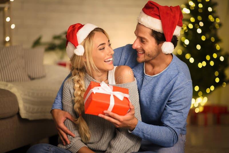 Χριστουγεννιάτικο δώρο Ευτυχισμένο ζευγάρι που γιορτάζει τα Χριστούγεννα στο σπίτι στοκ φωτογραφίες