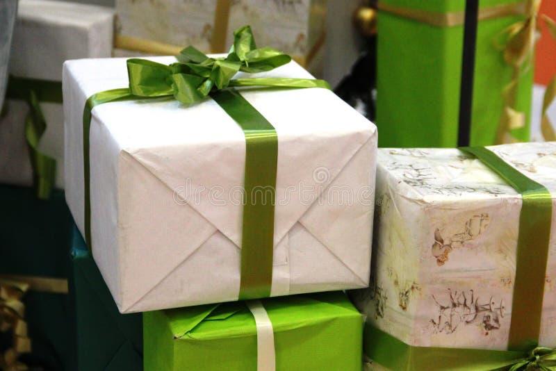 Χριστουγεννιάτικο δώρο κουτιά με δώρα, δεμένα με μια κορδέλα με ένα τόξο σχήμα με μπεζ και πράσινα χρώματα Δώρα Πρωτοχρονιάς στοκ φωτογραφίες