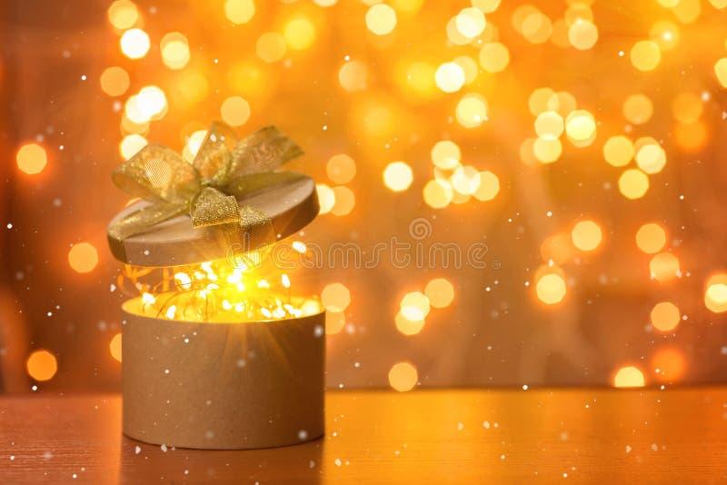 Χριστουγεννιάτικο δώρο στο μουτζουρωμένο υπόβαθρο φω'των στοκ φωτογραφίες