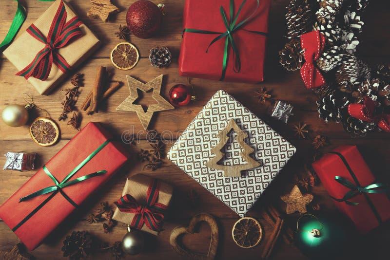 χριστουγεννιάτικο φόντο - τυλιγμένα δώρα και διακοσμήσεις σε ξύλινο τραπέζι στοκ φωτογραφία με δικαίωμα ελεύθερης χρήσης