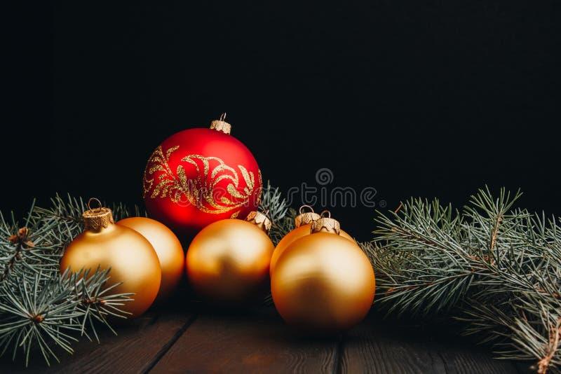 Χριστούγεννα ή νέοι σφαίρες διακοσμήσεων παιχνιδιών έτους χρυσοί και κλάδος δέντρων γουνών αγροτικός στο ξύλινο υπόβαθρο, τοπ άπο στοκ εικόνες με δικαίωμα ελεύθερης χρήσης
