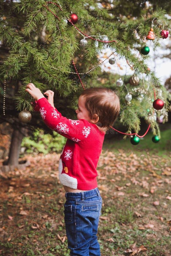 Χριστούγεννα καλές διακ& μικρό κορίτσι που διακοσμεί το χριστουγεννιάτικο δέντρο υπαίθριο στο ναυπηγείο του σπιτιού πριν από τις  στοκ εικόνες