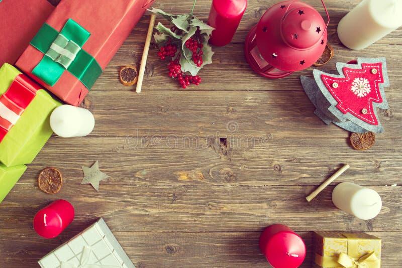 Χριστούγεννα καλές διακ& Ξύλινο υπόβαθρο Χριστουγέννων με τα δώρα, τα decotations και τα κεριά Τοπ όψη στοκ φωτογραφία