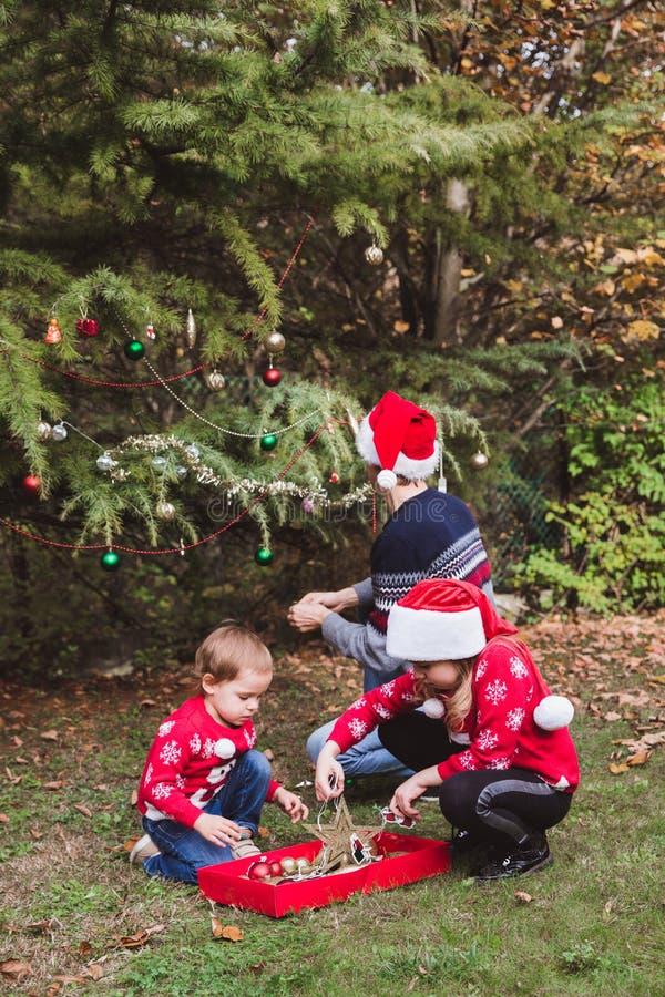 Χριστούγεννα καλές διακ& Πατέρας στο κόκκινο καπέλο Χριστουγέννων και δύο κόρες στα κόκκινα πουλόβερ που διακοσμούν το OU χριστου στοκ εικόνα με δικαίωμα ελεύθερης χρήσης