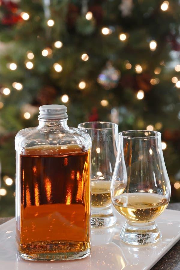 Χριστούγεννα μπουκαλιών ουίσκυ και Χριστουγέννων γυαλιών στοκ εικόνες