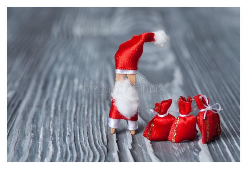 Χριστούγεννα, νέα κάρτα σχεδίου έτους Ξύλινο Clothespin Άγιος Βασίλης, παγετός πατέρων, μπαμπάς Noel με τα δώρα στοκ εικόνα
